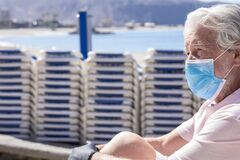 Free Senior Adult Man Wearing Protective Mask Due To Covid-19 Sitting Sadly At Deserted Beach With Closed Umbrellas And  Beach Beds - Stock Photos - 194047553