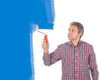 Senior adult painting wall in blue Royalty Free Stock Photo