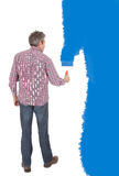 Senior adult painting wall in blue Royalty Free Stock Image