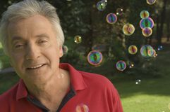 A senior adult playing with bubbles. Stock Image