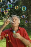 A senior adult playing with bubbles. Royalty Free Stock Image