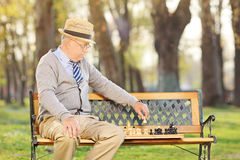 Senior adult playing chess outdoors Royalty Free Stock Photography