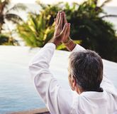 Senior adult practicing yoga by the pool stock photo