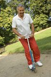 A senior adult on a push scooter. stock photography