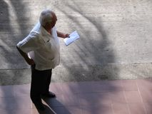 Senior adult standing on a street and looking to the side, aerial view.  Royalty Free Stock Photos