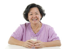 Senior adult woman drinking milk Stock Images