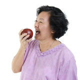 Senior adult woman eating apple. Elderly healthy diet. Portrait of happy 60s Asian senior adult woman eating an apple, isolated on white background Royalty Free Stock Photography