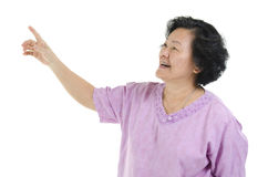 Senior adult woman finger pointing. Portrait of Asian senior adult woman smiling and hand pointing at blank copy space, isolated on white background Stock Photos