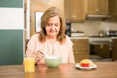 Senior adult woman forced to eat. Pretty senior woman sitting in the kitchen and without appetite for breakfast Royalty Free Stock Image