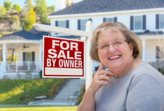 Senior Adult Woman in Front of Real Estate Sign, House Royalty Free Stock Photos