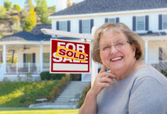 Senior Adult Woman in Front of Real Estate Sign, House Royalty Free Stock Image