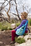 Field Trip Break. Senior adult woman in her late 60's sitting on a rock in the middle of the wilderness, taking a break from walking and absorbing the powerful Royalty Free Stock Photo