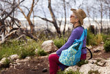 Field Trip Break. Senior adult woman in her late 60's sitting on a rock in the middle of the wilderness, taking a break from walking and absorbing the powerful Stock Photos