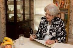 Senior Adult Woman Reading Magazine Royalty Free Stock Photos