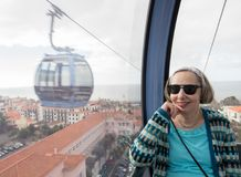 Senior adult woman riding in cable car over Funchal royalty free stock photos