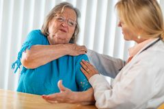 Pained Senior Woman Consults with Female Doctor About Sore Shoulder royalty free stock photo