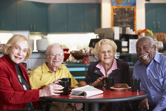 Senior adults having morning tea together royalty free stock photography