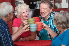 Senior Adults Toasting with Mugs Royalty Free Stock Photos