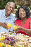 Senior African American Couple Drinking Juice. A happy, smiling men and women senior African American couple drinking orange juice & eating healthy food at a Stock Photo