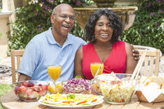 Senior African American Couple Eating Outside. A happy, smiling men and women senior African American couple eating healthy food at a picnic table outside Royalty Free Stock Image