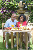 Senior African American Couple Eating Outside. A happy, smiling men and women senior African American couple eating healthy food at a picnic table outside Royalty Free Stock Images