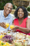 Senior African American Couple Healthy Eating Outs. A happy, smiling men and women senior African American couple eating healthy food at a picnic table outside Stock Photo