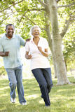 Senior African American Couple Running In Park Stock Image