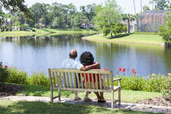 Senior African American Couple Sitting On Park Ben Stock Image