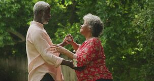 A senior african american couple spending time together dancing in the garden social distancing in q