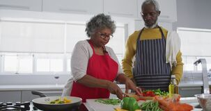 A senior african american couple spending time together at home cooking social distancing in quarant