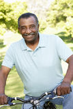 Senior African American Man Cycling In Park Stock Photo