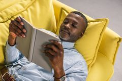 Senior african american man lying on sofa. And reading book stock photos