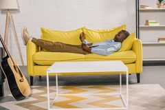 Senior african american man lying on sofa. And using laptop stock photos