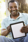 Senior African American Man In Park Using Tablet Computer Stock Images