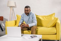 Senior african american man sitting on sofa and looking. At laptop royalty free stock photography