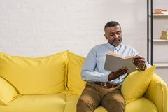 Senior african american man sitting on sofa. And reading book royalty free stock images