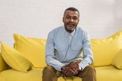 Senior african american man sitting on yellow couch and smiling. At camera stock photo