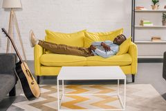 Senior african american man sleeping on yellow couch. At home stock photo