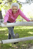 Senior African American Woman Exercising In Park Stock Photo
