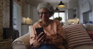 Senior african american woman using smartphone while drinking coffee while sitting on the couch at h
