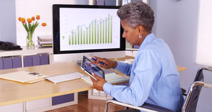 Senior African businesswoman multitasking at desk royalty free stock photography