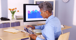 Senior African businesswoman multitasking at desk Stock Images