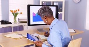 Senior African businesswoman multitasking at desk Royalty Free Stock Image