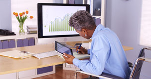 Senior African businesswoman multitasking at desk Stock Image