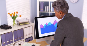 Senior african businesswoman standing and working at computer Stock Photos