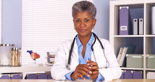 Senior african doctor sitting at desk looking at camera royalty free stock photos
