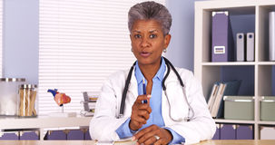 Senior african doctor sitting at desk and talking to camera stock photos
