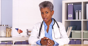 Senior african doctor sitting at desk and talking to camera royalty free stock photos