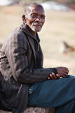 Senior African man. Old African resting on a stone, blurred African desert background Stock Image