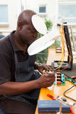 Senior african technician. Repairing a circuit board under electronic magnifying glass Royalty Free Stock Photos